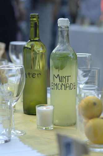 backyard wedding reception table beverages include water and mint lemonade in recycled wine glasses
