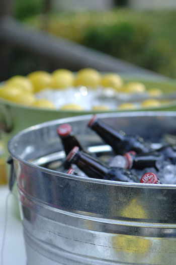 metal tins holding root beer bottles in ice at affordable backyard wedding