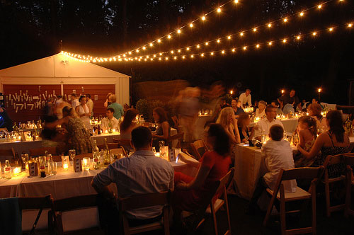 night photo of backyard wedding reception in driveway featuring candles and cafe lights