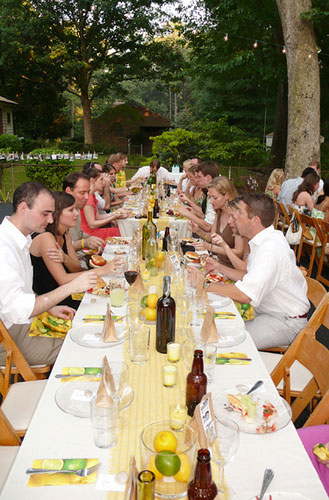 guests eating at $4000 backyard wedding reception at long family style tables with yellow and green theme